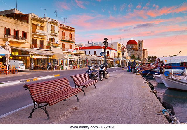 View of the seafront including Ekklisia Isodia Theotokou church and fishing boats in the harbour of Aegina island, Greece - Stock Image