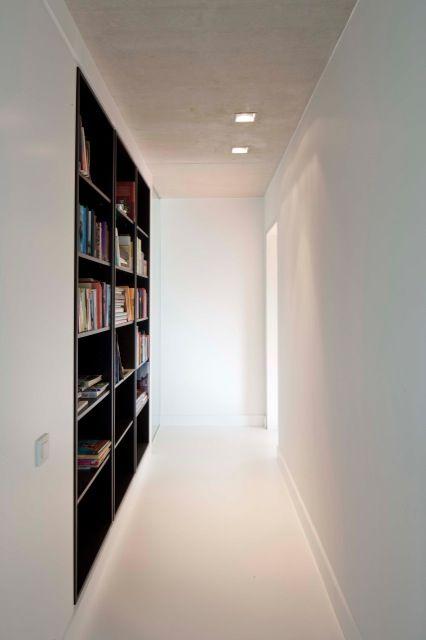 White corridor with dark, wooden bookshelves by Belgian interior architects Van Staeyen.