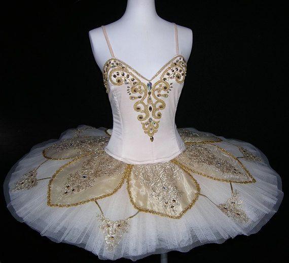 Tutú de ballet - tutú de ballet profesional de la etapa. Clásico de tutú blanco decorado por patrón de la flor dorada, recorte y pedrería. Puede ser utilizado para el ballet La bella durmiente. La blusa es de semi-estiramiento de blanco satén y tiene cierre de ganchos y ojos. El tutú está hecho en dos piezas blusa, falda del tutú y pedazos del brazo. La falda de tutu tiene 11 capas de blanco neto duro.  Esta es una costumbre hecha la orden. Se tarda 2-3 semanas para completar. Necesitamos…