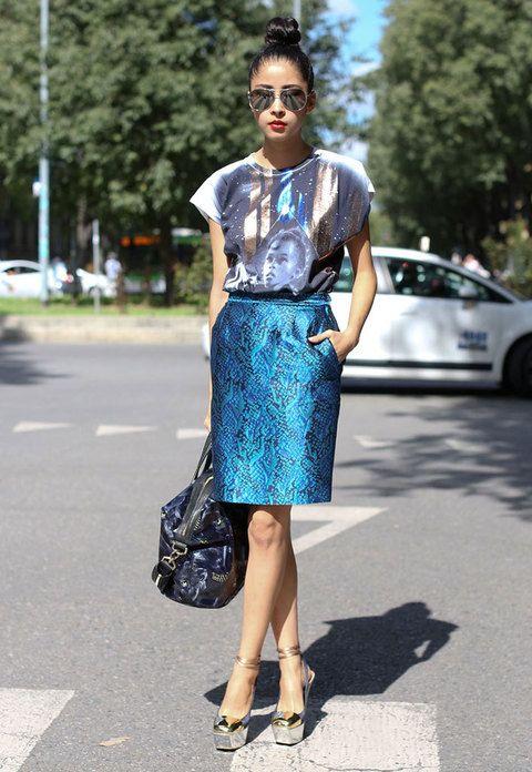 Falda estampada azul metálico y camiseta estampada con sandalias con plataforma metálicas. Gafas Ray-Ban y moño top knot rematan un look glamuroso.