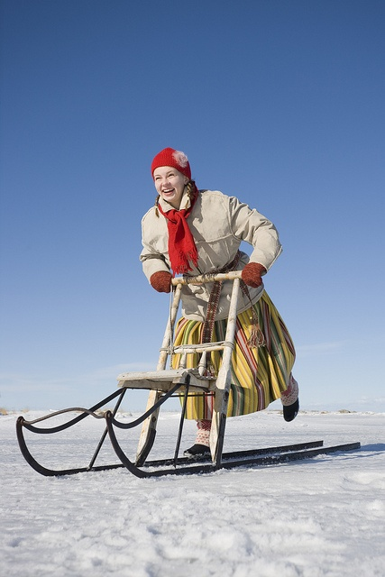 Europe | Portrait of a girl in traditional clothes riding kick sledge on the frozen sea, Estonia