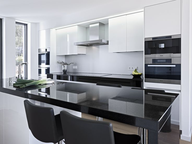 This modern black and white kitchen features Belgian Moon Caesarstone quartz countertops. Stunning interior design for a modern kitchen.