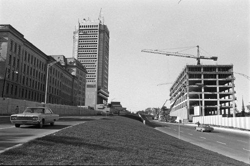Vue du boulevard Saint-Cyrille (René-Lévesque) et des abords en 1971. On distingue, à gauche, les édifices Honoré-Mercier, Jean-Antoine Panet, Marie-Guyart, le Grand Théâtre de Québec. De l'autre côté du boulevard, le premier bâtiment de Place Québec est en construction. (Construction de l'autoroute Dufferin-Montmorency à Québec, Jules Rochon - 1971-10, BAnQ, Fonds Ministère des Communications, E10,S44,SS1,D71-381, PE5)