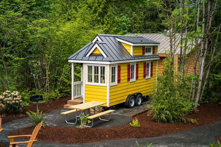 A white and yellow tiny home set in a campground in Oregon.   RePinned by : www.powercouplelife.com