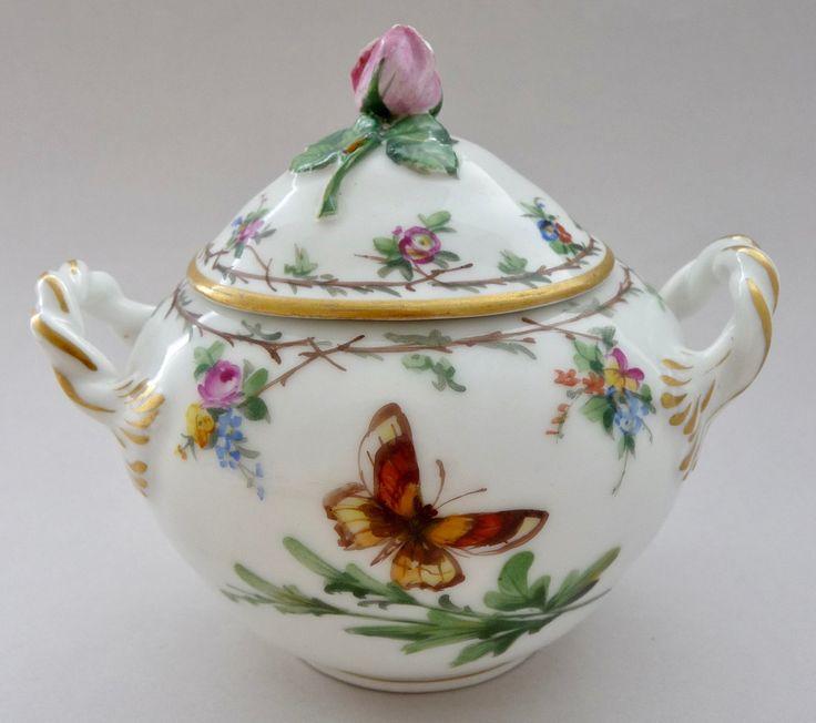 Royal Copenhagen ロイヤル・コペンハーゲン 1875年頃 シュガーポット  この楽しいシュガーポットは、スティーン・ノッテルマン, ロイヤル・コペンハーゲン・ ミュージアムの元館長によりますと1875年頃に製造されました。ポットの周りには幻想的な2匹の蝶が手描きで植物と描かれています。ポットと蓋の縁周りには、手描きの小さく折れた葉付きの小枝が繋がれて輪になり、その小枝の輪からはいくつかの小さな花飾り。そして、蓋のつまみは小さく愛らしいピンクのバラの蕾です。そばにはとても小さな1匹の昆虫が見られます。ハンドルは2本の紐をねじったような形で付け根の元の部分が盛り上がった葉模様になっています。
