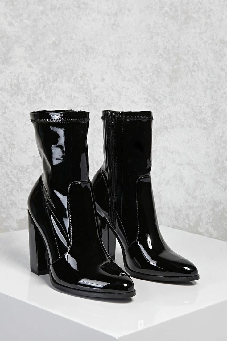 A pair of patent faux leather sock-style boots featuring a side zipper closure, pointed toe, and a chunky block heel.