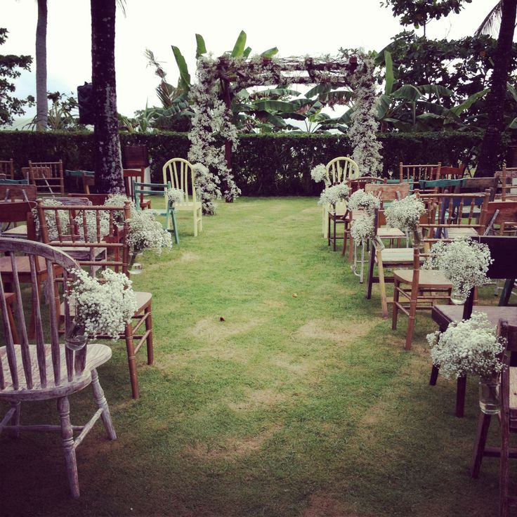 Baby's breath-adorned chuppah with ecletic chairs