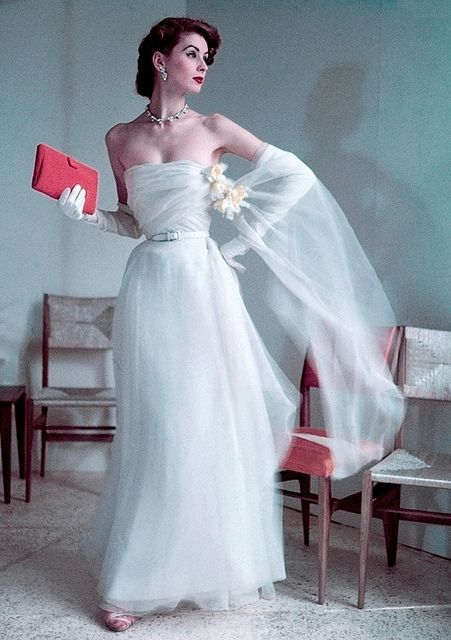 March 1952 Christian Dior long strapless ball gown which is nipped at the waist, and the chiffon stole is fastened with a daffodil corsage.