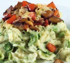 Andijviestamppot met gekookte aardappels, rauwe andijvie, geraspte kaas, gebakken spekjes en gekookt ei.