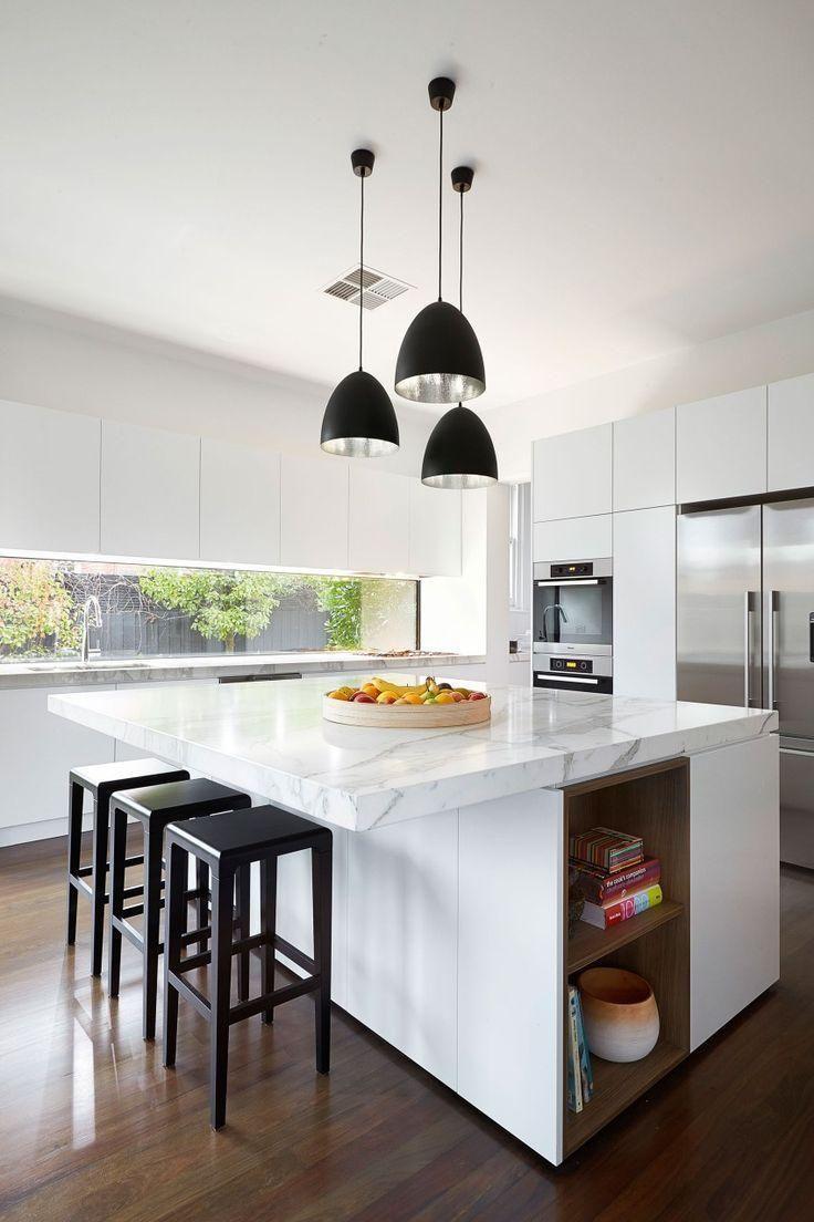 Cozinha contemporânea com luminárias pretas, bancada em ilha de mármore, banquetas pretas, armários brancos, piso de madeira, janela acima da pia. 37 Inspirações e Dicas de Decoração para Cozinha com Ilha