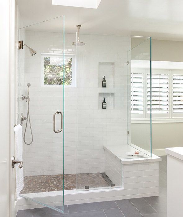 Beautiful bathroom features a walk-in shower fitted with white subway tiles fitted with stacked tiled shower niches over a marble shower bench. More