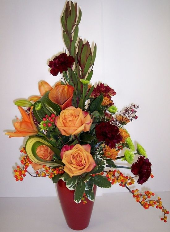 Arrangement with roses, safari sunset, asiatic lilies, callas, purple carns, green button mums, looped flax leaves and bittersweet vine.