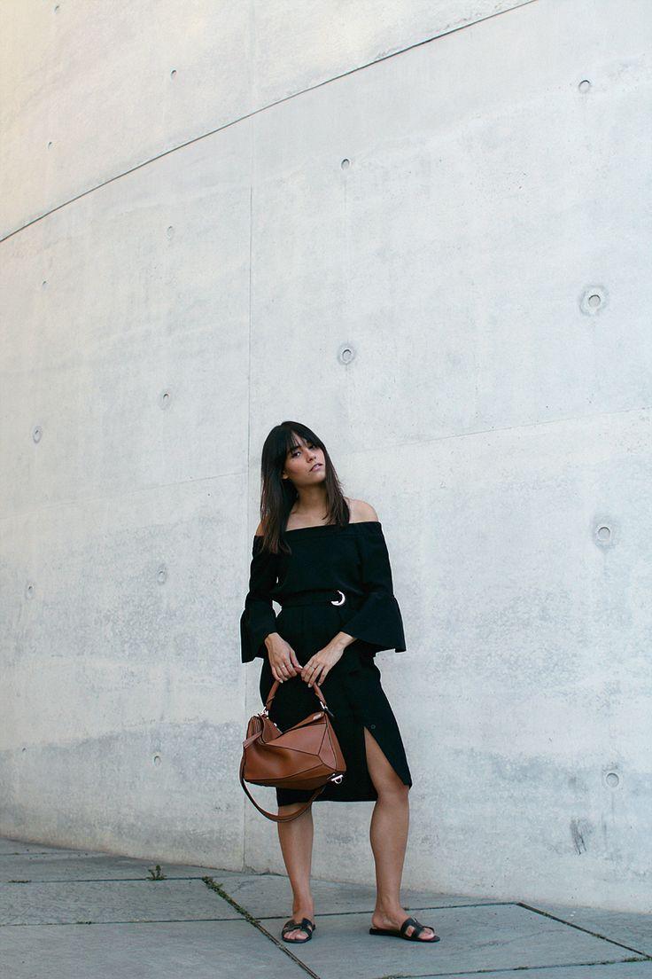 Nisi is wearing: Off-the-shoulder top with bell sleeves, midi skirt with slit, Hermès Oran sandals, Loewe Puzzle Bag