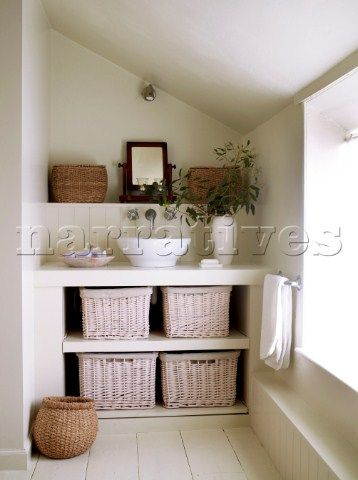 Built in unit with countertop wash basin and storage baskets in attic bathroom painted in neutral to