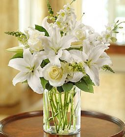 Classic All-White Arrangement Glorious roses lead the way in this luxurious white arrangement. Paired with lilies, snapdragons and salal, they're hand-gathered in a stylish cylinder vase to evoke an e
