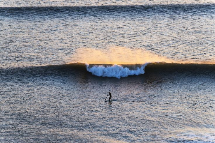 There is no escape for the paddleboarder as a large wave lit up by the sunset bears down upon him. Picture taken at the beautiful Kimmeridge Bay in Dorset, UK.  This particular image looks stunni...
