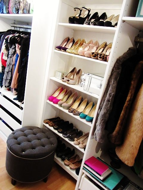 Gorgeous walk-in closet with built-in shoe storage, clothes rails and pull-out storage bins.