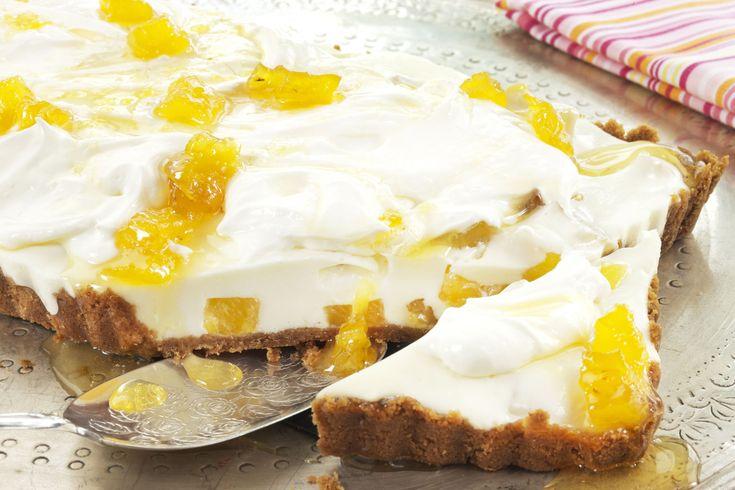 Bakelyst.no: Ostekake med lettere fyll av kremost og yoghurt naturell. Vispet creme fraiche på toppen. Ananassirup både i ostefyllet og som pynt på toppen av ostekaken.