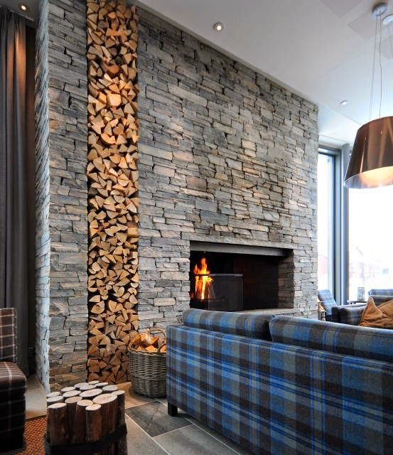 Rough-hewn stone fireplace with vertical strip of firewood piled up. Nice combination of precise geometric outlines & rustic textures.