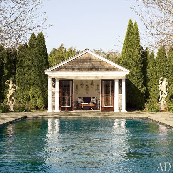 A pool house flanked by 19th-century Italian stone statues looks out to the pool | archdigest.com