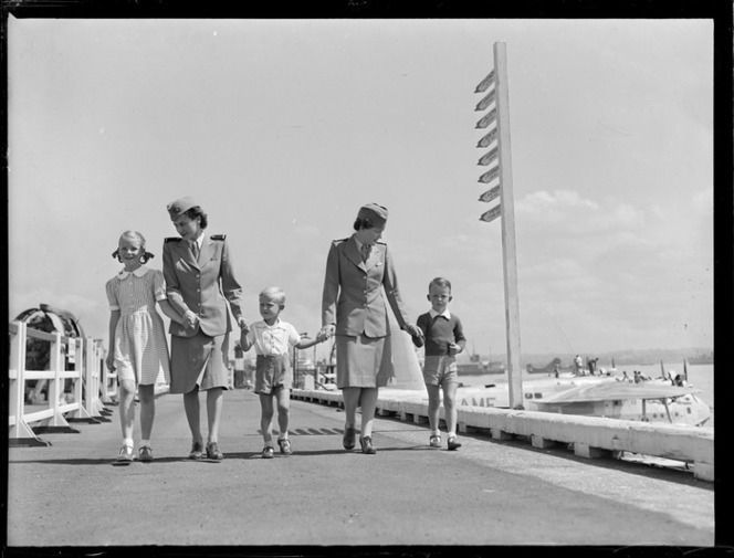 Unidentified children and stewardesses disembarking from the TEAL Short Tasman class Sunderland Flying Boat ZK-AME at Mechanic's Bay, Auckland City