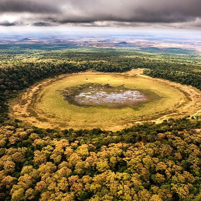 Photo @pedromcbride // The drying lakebed of Marsabit National Park in northern Kenya. This crater lake is an oasis for wildlife and water -- serving as a water tower for the region, but a changing climate combined with more straws in the water table have stressed and depleted this lake recently. #kenya #freshwater #aerial #climatechange #watertower #water #nature