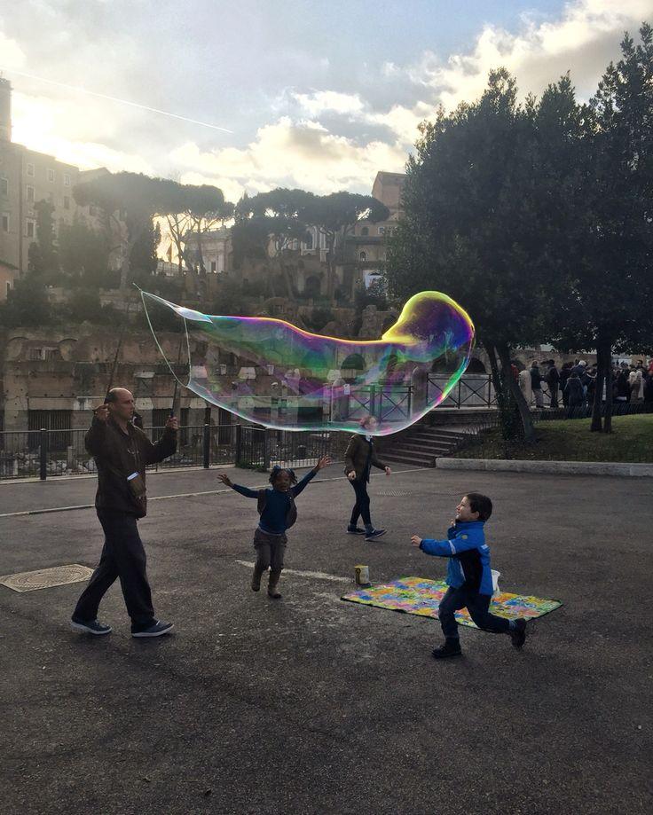 Giochi di strada   E mentre passeggi per la bellissima via dei Fori Imperiali, nel cuore di Roma, ti imbatti in alcuni bambini che si divertono a far scoppiare delle grandi bolle di sapone. ❤️