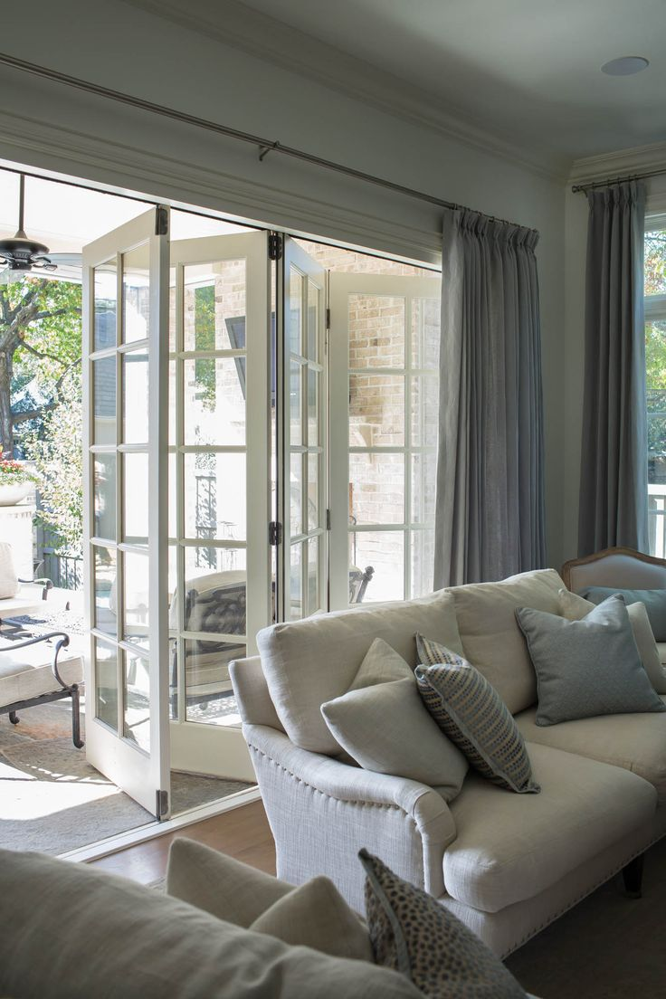 Accordion doors in family room leading out to the patio. English roll arm sofa. Neutral color palette.