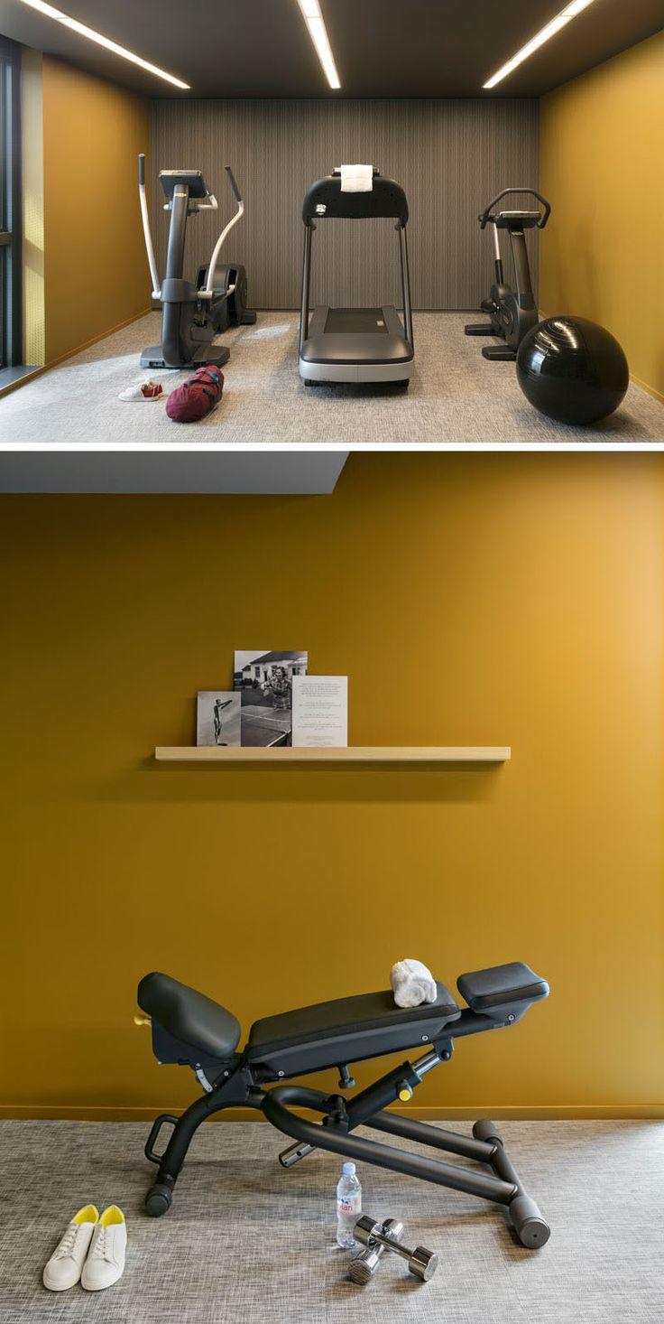 Современный тренажерный зал отеля имеет простой интерьер с яркими цветными стенами и полос освещения на потолке.