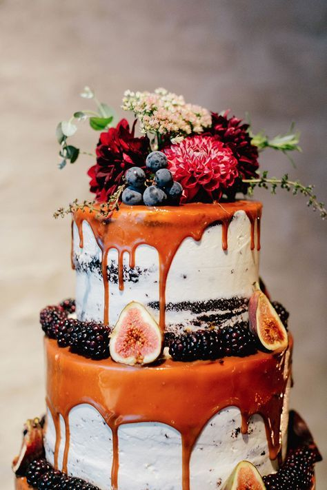 Gorgeous semi naked cake with caramel drip and beautifully adorned with figs, blackberries. Love the burgundy dahlia cake topper with grapes!