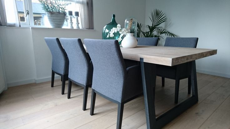 Big communal table and trendy chairs in eclectic dining room stock