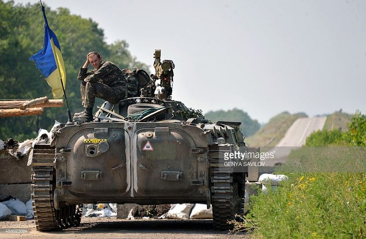 A Ukrainian serviceman sits on top of an armoured personnel carrier (APC) at a checkpoint near the eastern Ukrainian city of Debaltseve in the Lugansk region on August 1, 2014. Dutch and Australian experts finally got to work at the crash site of downed flight MH17 in eastern Ukraine, after fighting between government troops and pro-Russian rebels killed at least 14 people.