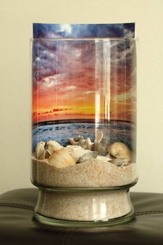 Sand and sea shells against a sunrise backdrop; in a jar. DIY  Like get stuff from the ground like cool rocks of the environment and a pic like of you doing the poses like this is so cool Shan you should totally do it