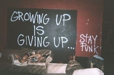 "Writing in grafitti on a club wall reading ""Growing Up Is Giving Up...Stay Punk."" A girl sleeps on a velvet sofa in front of the sign."