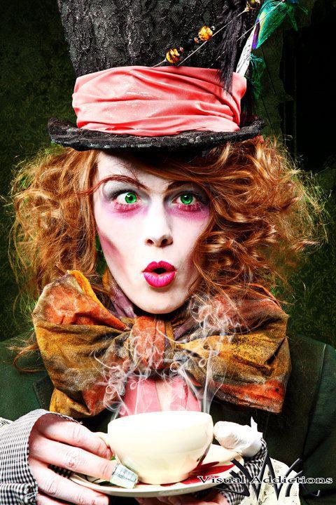 Pink eye shadow, big bow necktie, massive hat with sign, waistcoat and frockcoat/velvet jacket. Crazy orange hair.