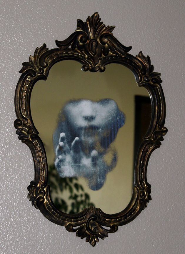 Easy to do; just sand the mirror on the back until you can see through it, or use oven cleaner and a utility knife. Then attach your favorite spooky picture.