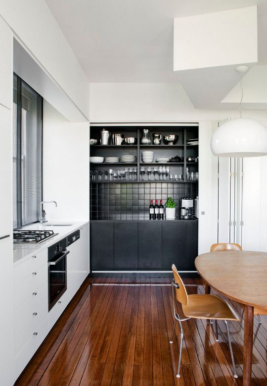 A very simple, modern kitchen with a wooden floor that stands out. #kitchen #wood #white #black #modern