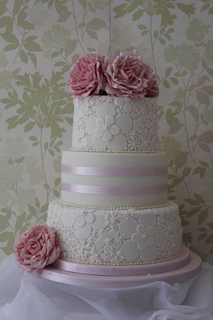 A three tier wedding cake with 2 embossed tiers and flowers, Love this one, but in purple obviously, with the purple ombre cake inside :]