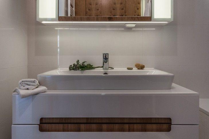Aranżacja wnętrza małej, białej łazienki z dodatkiem drewna –Tissu. W pomieszczeniu dominują biele porcelany i kafli ściennych. Drewniane detale dodają przytulności. http://www.tissu.com.pl/zdjecia/120