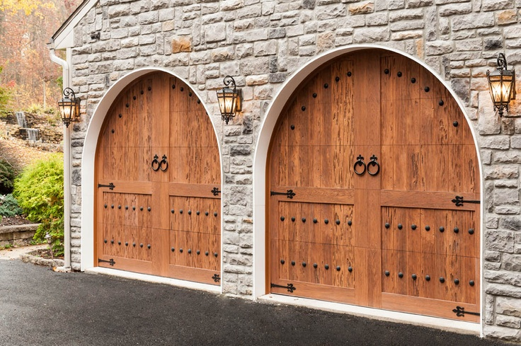 Decorative hardware makes these Clopay Canyon Ridge Collection faux wood carriage house garage doors fit for a man's castle - his garage. Model shown: Design 11, Medium Finish, with Ring Door Knockers, Fleur de lis Strap Hinges and Round Clavos. Installed by County Garage Door in SE Pennsylvania. www.clopaydoor.com.