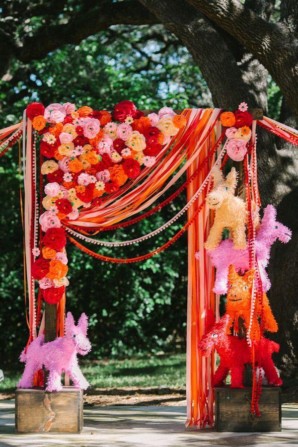 Pink and orange photo backdrop with pinatas