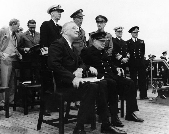 Conference leaders during Church services on the after deck of HMS Prince of Wales, in Placentia Bay, Newfoundland, during the Atlantic Charter Conference. President Franklin D. Roosevelt (left) and Prime Minister Winston Churchill are seated in the foreground. Standing directly behind them are Admiral Ernest J. King, USN; General George C. Marshall, U.S. Army; General Sir John Dill, British Army; Admiral Harold R. Stark, USN; and Admiral Sir Dudley Pound, RN.