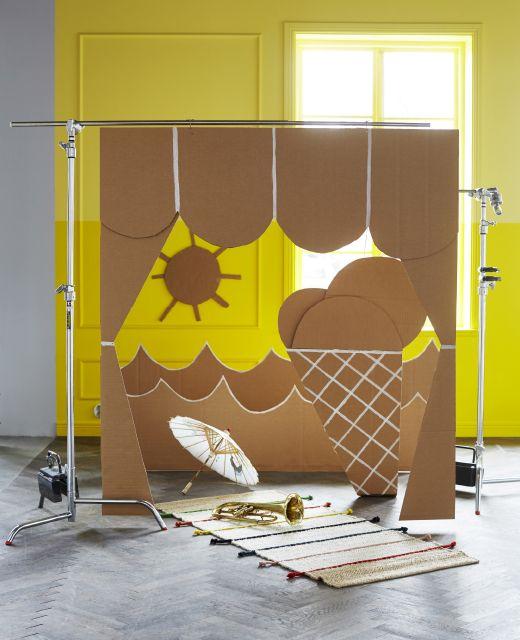 Escenario de un teatro infantil hecho con cartón y colgado de una barra.