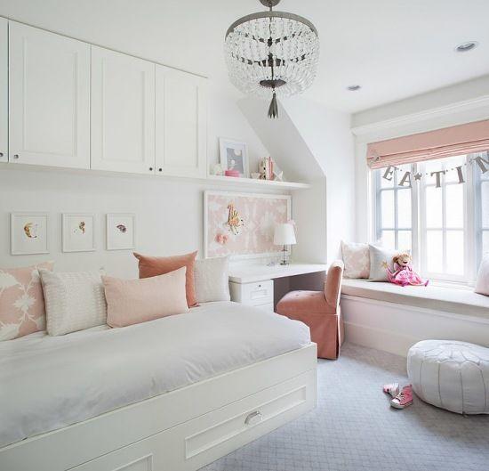 białe łóżko z szafkami na ścianie,małe biurko i zabudowa z siedziskami przy oknie z różową roletą i poduszkami dekoracyjnymi - Lovingit.pl