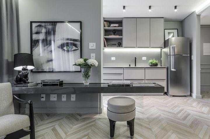 Na cozinha, o que chama atenção é o contraste da madeira ebanizada com os linhos claros, cobre e latão no mobiliário e luminárias. No piso, a madeira na clássica paginação Chevron