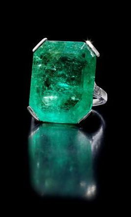 An art deco emerald ring, circa 1920 The step-cut emerald, weighing 19.15 carats, between shoulders set with trios of brilliant-cut diamonds, mounted in platinum
