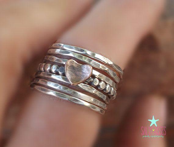 Esta ha sido la mano cortar, soldar, incendiaron y cayó por la fuerza por mí en mi estudio de Denver, CO. Dio el anillo de perlas corazón acabado un mate/satinado oxidado. Puedo también enviar este conjunto brillante sin pátina.   Se trata de un sistema de 7 anillos. Una plata abalorios anillo con un corazón de cobre y seis apiladores de plata con textura.  El corazón de cobre es aproximadamente de 5.5 x 6.5 mm. Si quieres que un juego como este con un corazón un poco más grande, por favor…