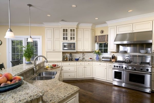 santa cecilia light granite countertops white kitchen cabinets stainless steel appliances pendants