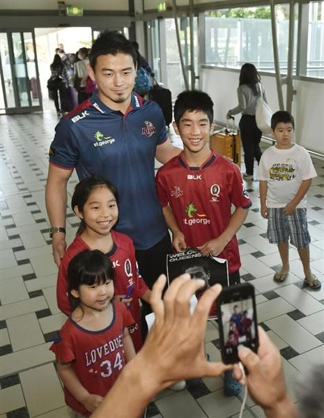 オーストラリアのブリスベンに到着し、地元ファンの子どもたちと記念写真に納まるラグビーの五郎丸歩=6日(共同)