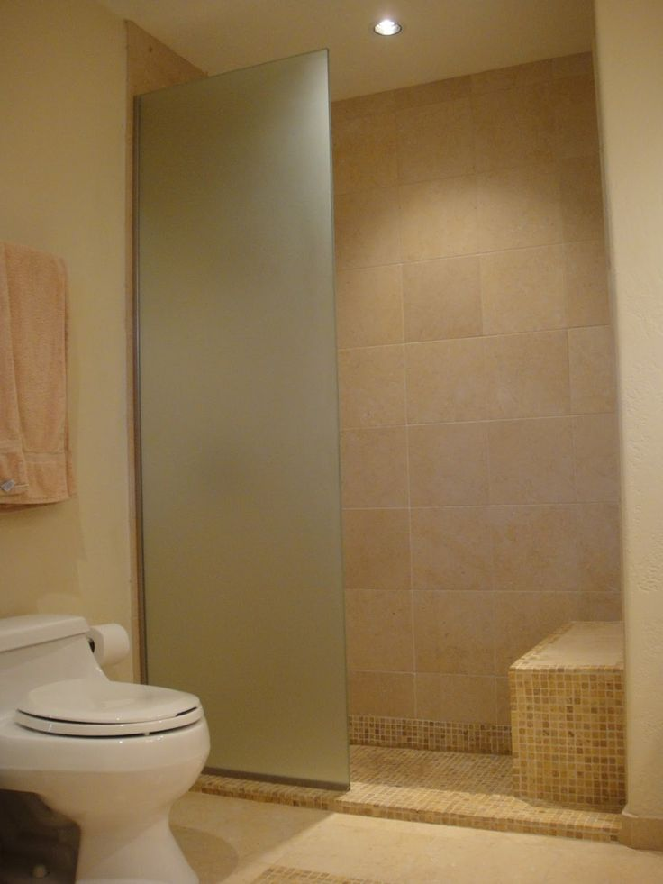 shower bathroom limestone with shaped glass partition and white toilet